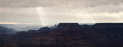 Sunlight breaking through clouds over the Grand Canyon - p1515m2101073 by Daniel K.B. Schmidt