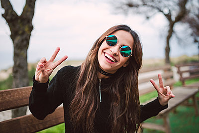Portrait of young woman wearing mirrored sunglasses showing victory signs - p300m1228328 by Ramon Espelt