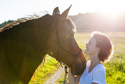 Profiles of young woman and horse at backlight - p300m1460343 by Tom Chance