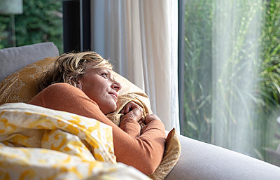 Mature woman looking through window while lying on sofa at home - p300m2240041 by Bernd Friedel