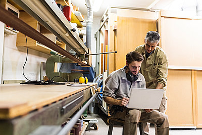 Male colleagues discussing on laptop while working at workshop - p300m2293668 by Eugenio Marongiu