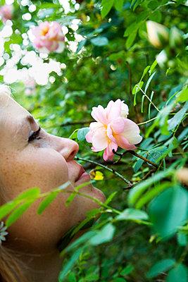 Teenage girl (16-17) smelling flowers - p352m2119629 by Lena Katarina Johansson