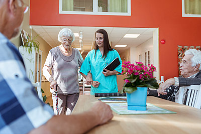 Senior woman and nurse walking arm in arm towards friends at nursing home - p426m2072553 by Kentaroo Tryman