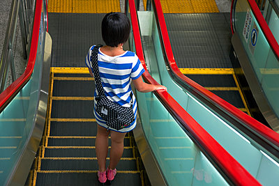 A detailed view shows a  stylish young woman riding an escalator below a platform of the Yamanote Line (a 34.5 km double-track loop railway serving an estimated 3.68 million passengers daily from before dawn until after midnight, encompassing the line's 2 - p855m1122265 by Ben Simmons