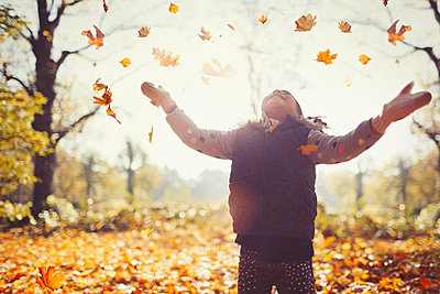 Playful girl throwing autumn leaves overhead in sunny park - p1023m1402965 by Paul Bradbury