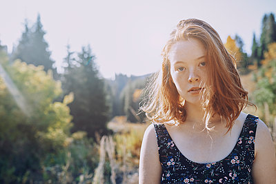 Portrait confident young woman in sunny park - p1023m2088003 by Arman Zhenikeyev