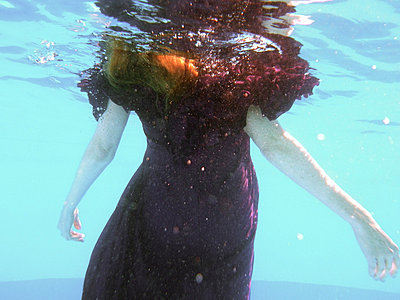 Woman wearing purple dress underwater her arms stretched out to the sides. - p1072m829545 by Tracy Jean Shields