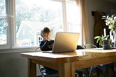 Little boy in morning light sitting at table doing remote school - p1166m2232706 by Cavan Images