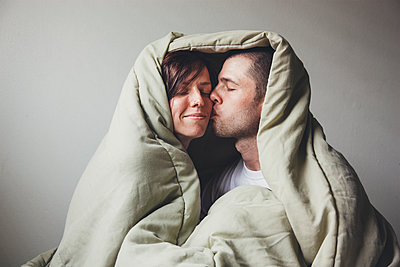 Couple Cuddling Under Blanket - p1262m1125263 by Maryanne Gobble