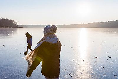 Germany, Brandenburg, Lake Straussee, two kids walking on frozen lake - p300m1581269 by Julia Otto