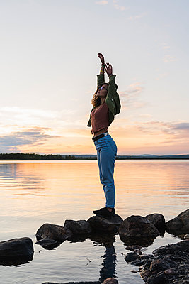 Finland, Lapland, woman standing at the lakeside at twilight - p300m2060820 by Kike Arnaiz