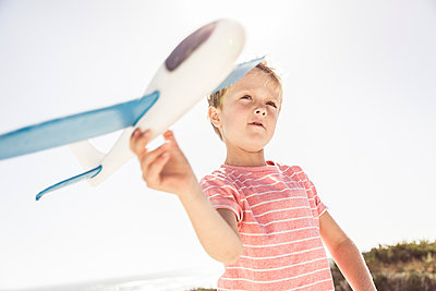 Boy playing with toy plane - p300m2166965 by Floco Images