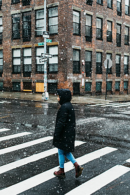 Young woman in warm jacket crossing snowy urban street, New York City, New York, USA - p301m2213635 by Toby Mitchell