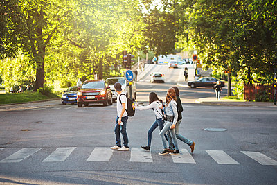 Side view of teenagers crossing road - p426m1085570f by Maskot