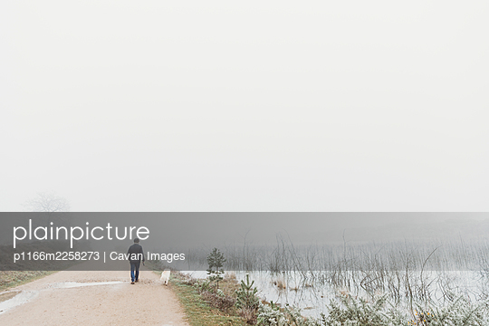 Rear view of man with dog walking by lake in fog - p1166m2258273 by Cavan Images