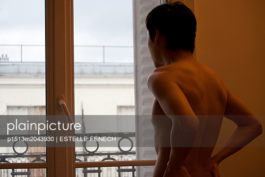 Young man at the window - p1513m2043930 by ESTELLE FENECH