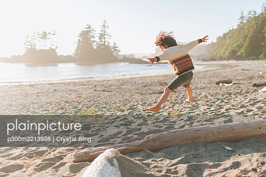 Boy with arms outstretched jumping at beach - p300m2213938 by Crystal Sing