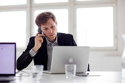 Junger Geschäftsman mit Handy am Schreibtisch - p1212m1115661 von harry + lidy