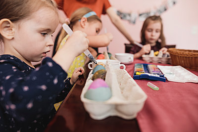 Girls painting Easter eggs on table at home - p300m2103452 by Katharina Mikhrin