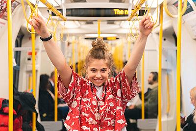 Portrait of happy young woman in the metro - p300m2121947 von William Perugini