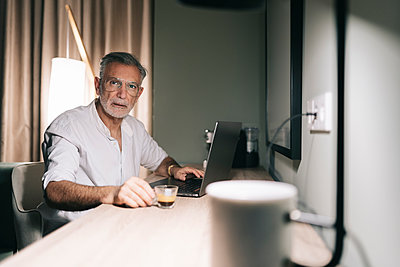 Mature man holding coffee cup while sitting at desk with laptop in hotel room - p300m2250489 by Daniel González