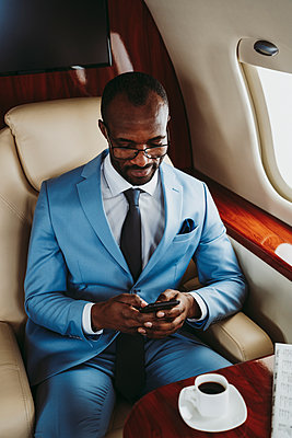 Young male entrepreneur text messaging on mobile phone in private jet - p300m2256371 by OneInchPunch