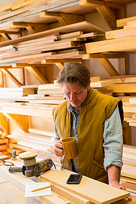 Caucasian carpenter drinking coffee and using cell phone in workshop - p555m1301772 by Marc Romanelli