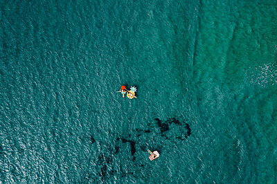 Three women on air mattress in the sea, drone photography - p713m2289223 by Florian Kresse