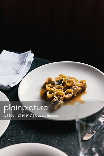 Stuffed pasta and sage from the side in moody restaurant table - p1166m2191917 by Cavan Images