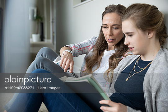 Mother helping teenage daughter with homework - p1192m2088271 by Hero Images