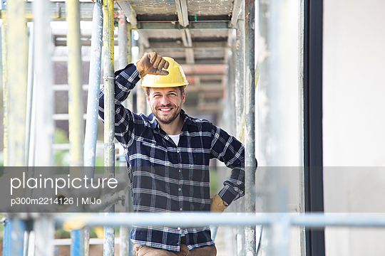 Smiling construction worker wearing helmet standing by scaffold at construction site - p300m2214126 by MiJo
