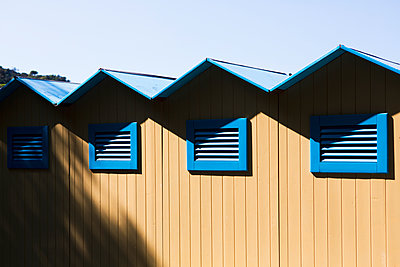 Simple beach huts and shelter with blue sky paint din bright colours on the north Italian coast. - p1057m2164316 by Stephen Shepherd