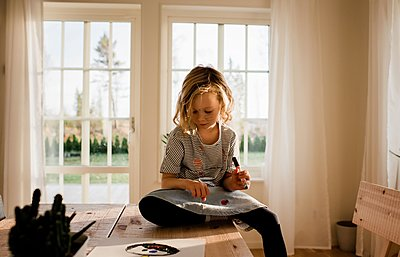 young girl drawing on her hand and face at home - p1166m2148539 by Cavan Images