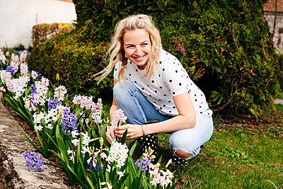 Young blonde woman controls hyacinths in her garden - p300m2103727 von Epiximages