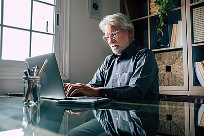 Serious senior male entrepreneur with eyeglasses using laptop in home office - p300m2277628 by Simona Pilolla