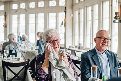 Senior woman crying while male friend smiling in restaurant - p426m2149129 by Maskot