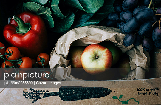 fresh organic fruit and vegetables in a recyclable box freshly picked - p1166m2255390 by Cavan Images