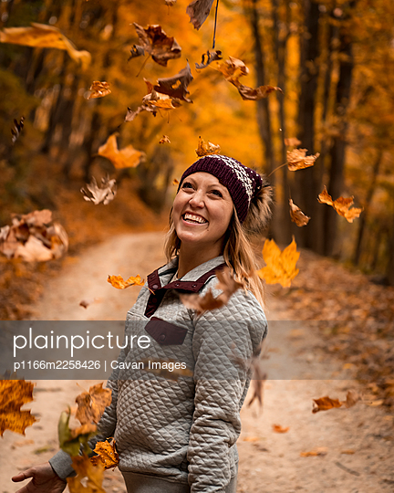 Cheerful young woman throwing autumn leaves while enjoying vacation in forest - p1166m2258426 by Cavan Images