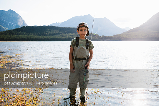 Portrait confident boy fishing at sunny lake - p1192m2129178 by Hero Images