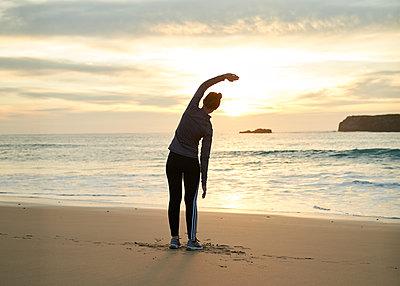 Dehnübung am Strand - p1124m1112575 von Willing-Holtz