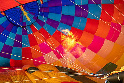 Flames heat the air trapped in a hot air balloon prior to take off - p1166m2111610 by Cavan Images