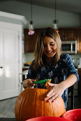 Girl scooping pumpkin seeds out of a pumpkin at halloween - p1166m2269355 by Cavan Images