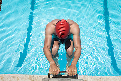 Young Caucasian male swimmer holding starting block in swimming pool - p1315m2091036 by Wavebreak