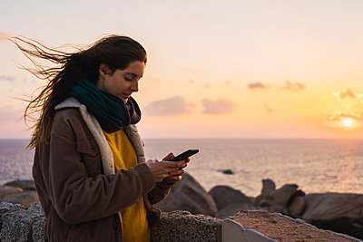 Italy, Sardinia, woman using cell phone at the coast at sunset - p300m1581282 von Kike Arnaiz