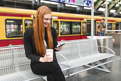 Redheaded young woman with coffee to go waiting at platform using smartphone, Berlin, Germany - p300m2141002 by William Perugini