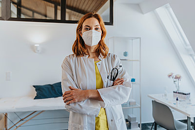 Confident healthcare worker wearing protective face mask standing with arms crossed at clinic - p300m2267726 by Mareen Fischinger