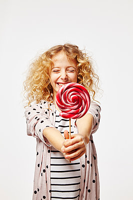 Blonde girl holding red lollipop - p968m1128437 by Roberto Pastrovicchio