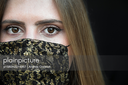 Young woman with fashionable mask in gold and black - p1580m2214957 by Andrea Christofi