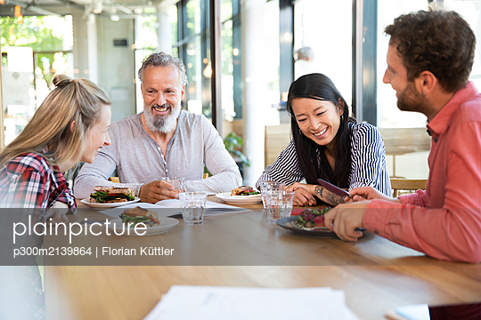 Happy casual business people having business lunch in a cafe - p300m2139864 von Florian Küttler