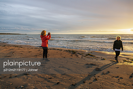 Woman taking photo on beach - p312m2119177 by Johner